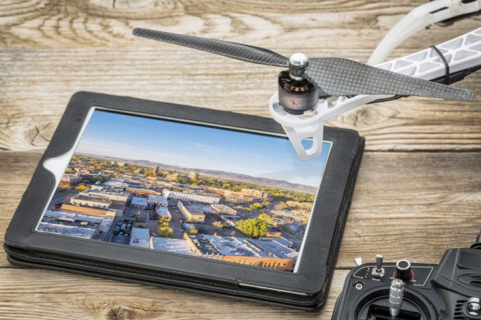 St Louis Drones aerial photography - reviewing aerial pictures on a digital tablet with a drone rotor and radio control transmitter,